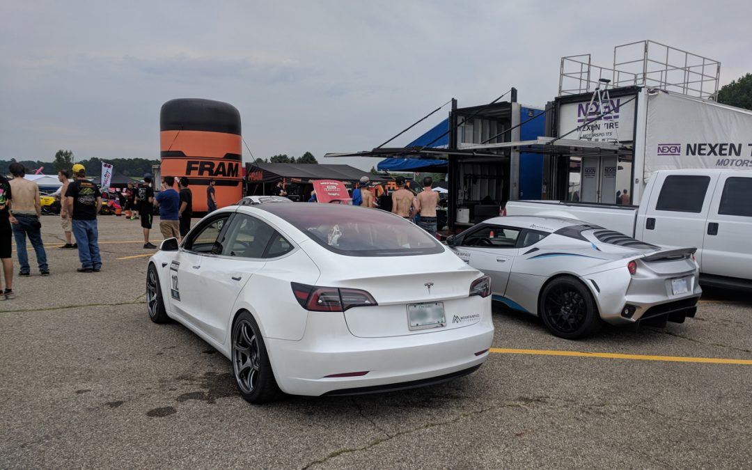 Tesla Model 3 and Tesla Powered Lotus Evora hanging out at gridlife waiting for Chris Forsberg